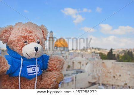 Teddy Bear On A Sunny Day On The Background Of The Golden Dome And The Wailing Wall In Jerusalem. To