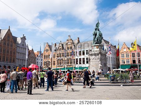 Bruges, Belgium - June 3, 2017:  Tourists Are Resting On The Grote Markt Square Near Statue Of Jan B