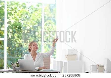Young Woman With Air Conditioner Remote In Office