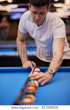 Man in white polo-neck shirt aligns balls in line along cue stick on pool table in club, focus on red ball.