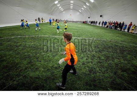 Boy goalkeeper at goal box during soccer game, side view.