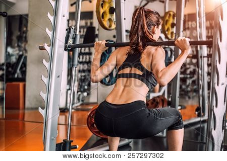 Beautiful Sporty Sexy Woman Doing Squat Workout In Fitness Gym Workout Training Center Sport Club. B