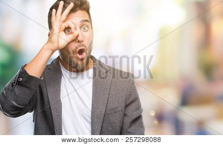Young handsome business man over isolated background doing ok gesture shocked with surprised face, eye looking through fingers. Unbelieving expression.