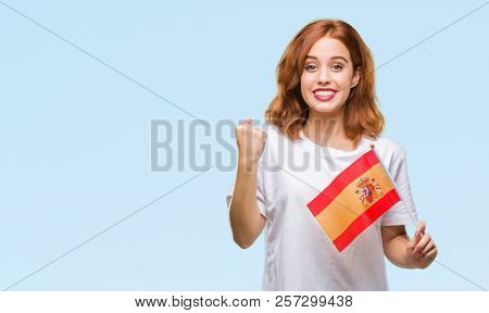 Young beautiful woman holding flag of spain over isolated background screaming proud and celebrating victory and success very excited, cheering emotion