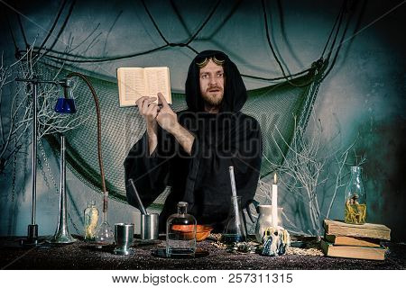 Portrait Of A Crazy Alchemist. The Medieval Scientist Indicates The Text In The Recipe Book. Hallowe