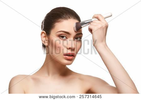 Girl Applying Foundation On Face Isolated On White