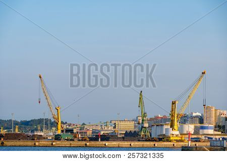 Three Heavy Cranes, Two Yellow And One Green Used For Loading Merchant Ships In The Port Of La Corun