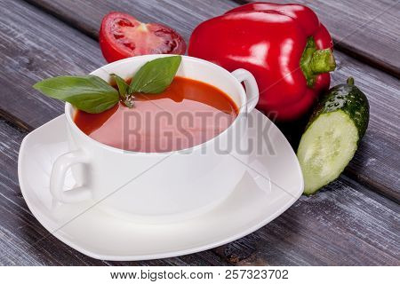 Tomato Cold Soup In A White Plate On A Wooden Background