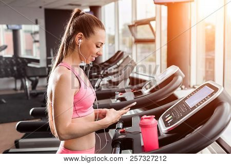 Slim Beautiful Woman With A Ponytale Standing On The Treadmill In The Gym Holding A Phone Wearing Ea