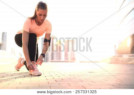 Young Fitness Attractive Sporty Girl Runner Ties Up The Shoelaces On Her Sports Shoes Getting Ready