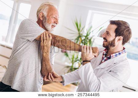 Man Having Chiropractic Arm Adjustment. Physiotherapy, Sport Injury Rehabilitation. Senior Man Exerc