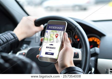 Ride Share Driver In Car Using The Rideshare App In Mobile Phone. New Taxi Ride Request From Custome