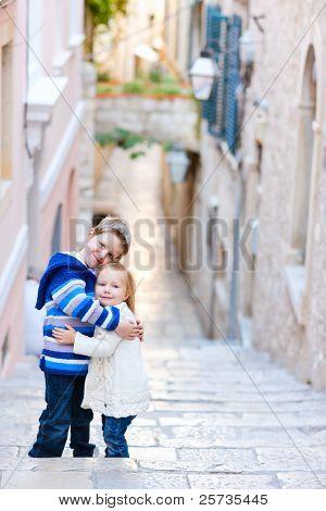 Brother and sister hugging and posing at narrow street in Dubrovnik Croatia