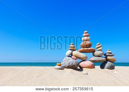 Rock Zen Pyramid Of Colorful Pebbles On A Sandy Beach On The Background Of The Sea. Concept Of Balan