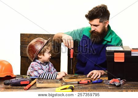 Father&son in workshop. Handcrafting, repair, craftsman. Kid boy play in handyman. Cute kid exploring tools. Father, parent teaching son to use screwdriver. Dad&son. Teamwork concept. Little assistant poster