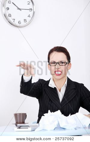 Pretty caucasian mad businesswoman throwing paperball in the office.