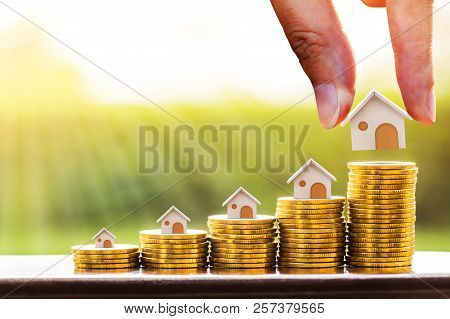 Woman Hand Hold A Wooden Home Model Put On The Stack Coin With Growing In The Public Park, Savings M