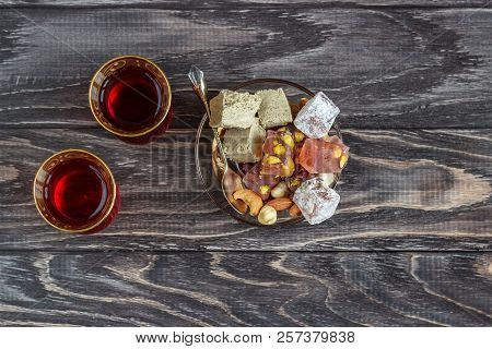Turkish joys with different nuts is a glass of tea and a spoon. Eastern sweets. Traditional Turkish delight (Rahat lokum) on a wooden background. View from above poster
