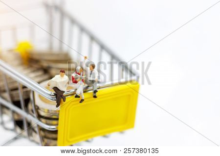 Miniature People: Businessmen Reading On Shopping Cart With Coins. Shopping And Business Concept.