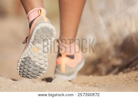 Young Woman With Athletic Sneakers Jogging Or Running Nature.female Athlete Runs On Mountain Rocky P