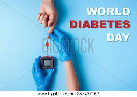 Inscription World Diabetes Day, Nurse Making A Blood Test. Man's Hand With Red Blood Drop And Glucos