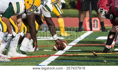 Two High School Football Teams Are Lined Up For The Snap Of A Play During A Football Game On A Green