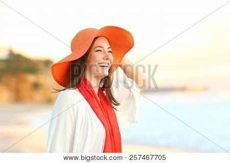 Happy Woman Wearing An Orange Picture Hat Contemplating Ocean On The Beach