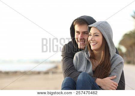 Happy Couple Of Teens Hugging And Looking At Horizon On The Beach