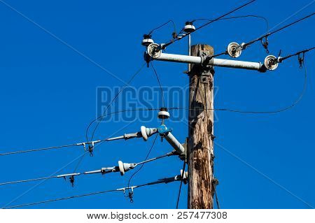 Old Power Pole With Insulators And Wires Against A Blue Sky