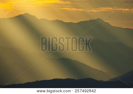 Dramatic God Lights Passing Through Clouds And Shining On Mountain Ranges. Warm Light Shower.