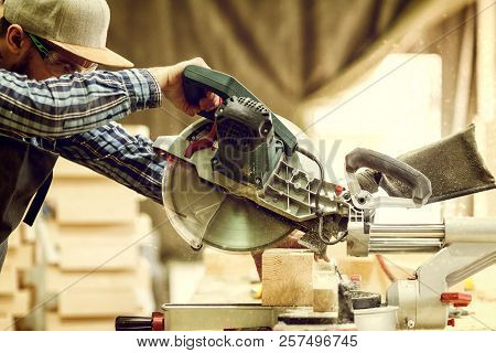 Close Up A Carpenter In Work Clothes  Doing Woodwork In Carpentry. Small Buiness Owner Cut On Wood P
