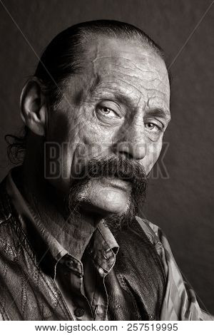 A Gritty Looking Man With A Horseshoe Mustache And Black, Leather Jacket.  He Has His Mouth Partiall