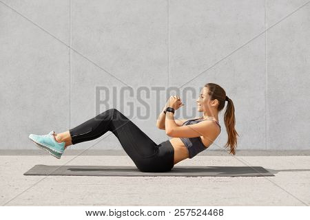 Self Determined Sporty Woman With Pony Tail, Dressed In Leggings, Top, Sneakers, Smartwatch Makes On
