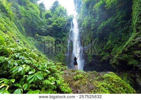 Woman enjoying and relaxing in front of the Laangan waterfall in the Munduk forest, Bali island, Indonesia