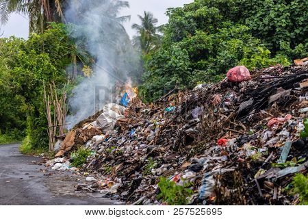 Tons of industrial rubbish burning along the road in the Banda Neira island, Indonesia