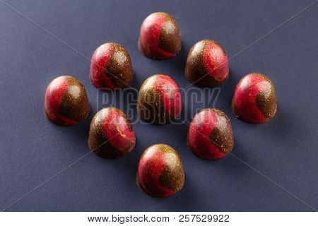 Red And Gold Colored Luxury Handmade Chocolate Candy On Black Background. Exclusive Handcrafted Bonb