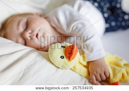 Cute Adorable Baby Girl Of 6 Months Sleeping Peaceful In Bed At Home. Closeup Of Beautiful Calm Chil