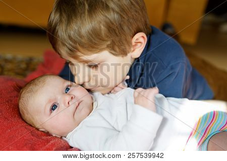 Close-up Portrait Of Happy Little Kid Boy With Newborn Baby Girl, Cute Sister. Siblings. Brother And