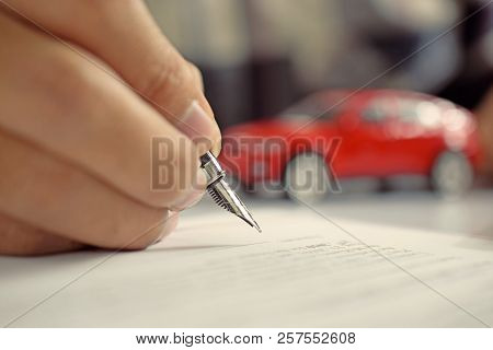 Man Signing Car Insurance Document. Writing Signature On Contract Or Agreement. Buying Or Selling Ne