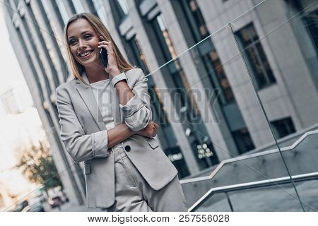 Good Business Talk. Beautiful Young Woman In Suit Talking On The Phone And Smiling While Standing Ou