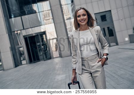 Business Is Her Life. Beautiful Young Woman In Suit Pulling Luggage And Smiling While Walking Outdoo