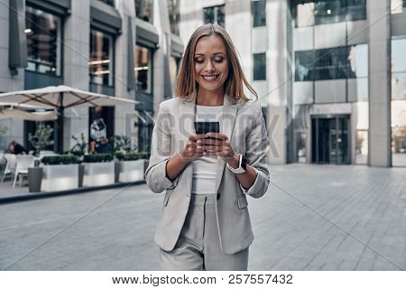 Chat With Client. Beautiful Young Woman In Suit Using Smart Phone And Smiling While Standing Outdoor