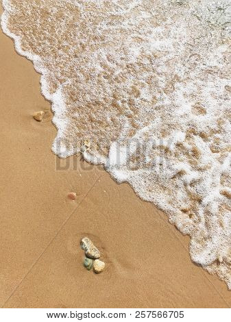 Wave Of Sea On A Sand Beach. The Wave Washes The Golden Sand Of The Beach. White Foamy Waves Of The