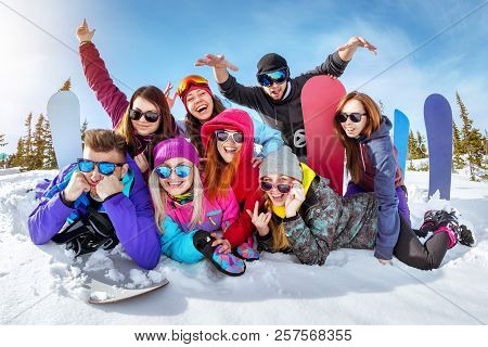 Happy Friends Skiers And Snowboarders Having Fun At Ski Resort. Winter Vacations Concept