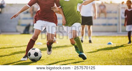 Boys Play Football. Running Football Soccer Players. Kids At Soccer Field Running With Ball. An Acti