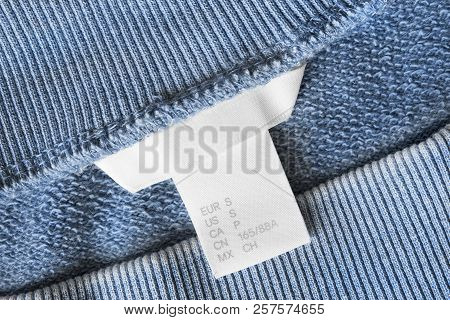 Small Size Clothes Label On Blue Textile Background Closeup