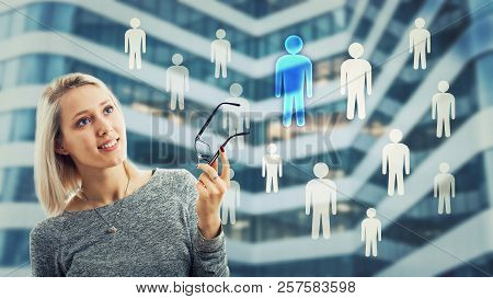 Smiling Woman Holding Glasses And Thinking About Staff Choice. Choosing A Different Person From The
