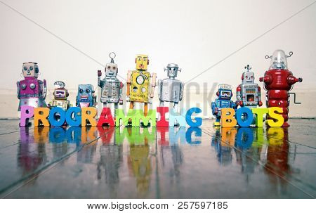PROGRAMMING BOTS wooden letters and retro robot toys on a wooden floor with reflection
