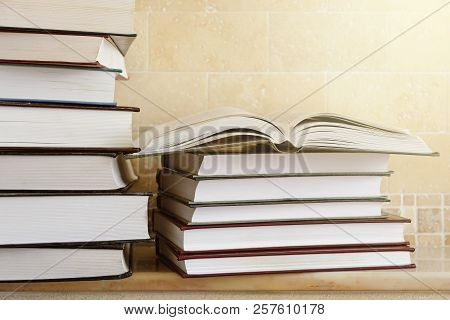 Pile Of Books With Open Book On Marble Shelf. Bookshelf With Piled Books.