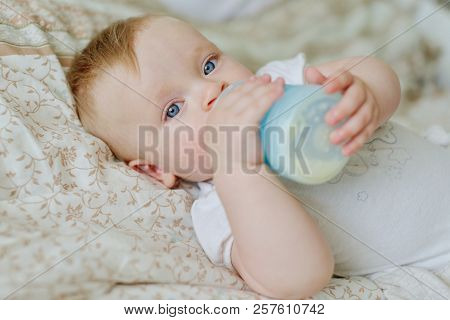 A Little Baby With A Bottle On The Bed